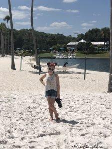 girl standing in sand at Swan resort in Walt Disney World-disney trip report
